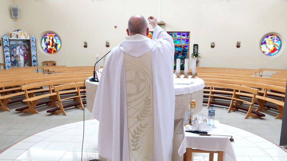 A priest celebrating Mass in an empty church during the first lockdown