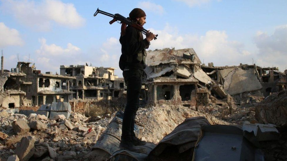 A rebel fighter stands amid the rubble of destroyed buildings in a rebel-held area of Deraa, in southern Syria, on 14 March 2017