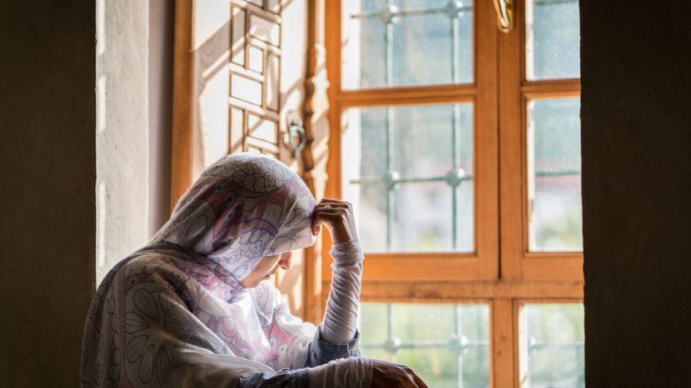 Person in a hijab looking out a window