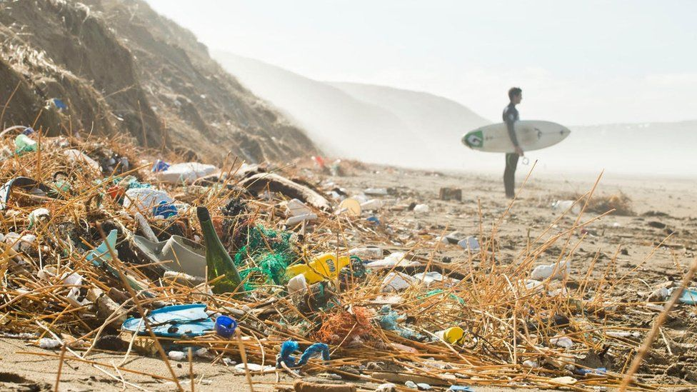 A surfer stands near a mound of plastic litter on a beach in Cornwall