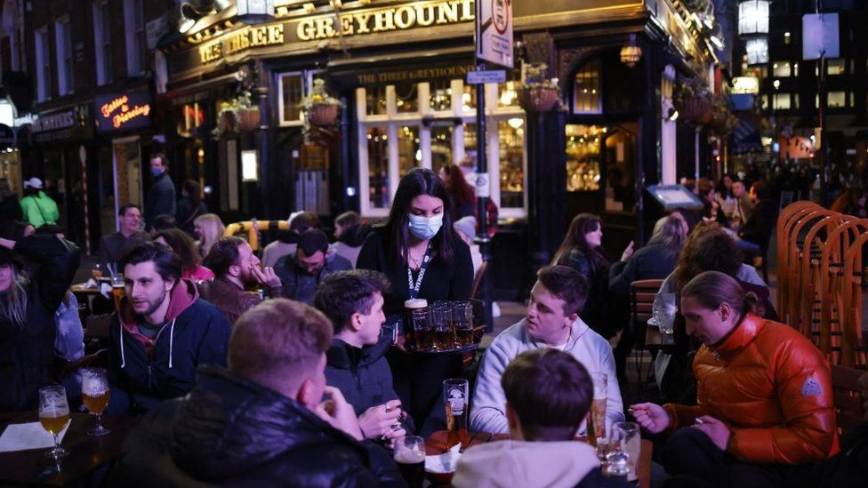 Drinkers enjoy pints at a pub in London