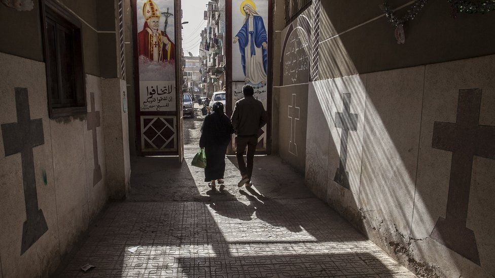 a man and woman walking through a sun-lit street with crosses and Christian motifs on the walls, file pic