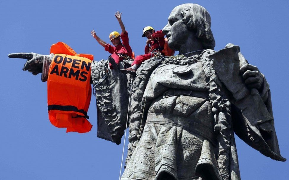 """Activists place a lifejacket on the arm of the Columbus monument in Barcelona as the rescue vessel """"Open Arms"""" arrives in the city"""