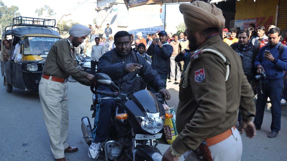Indian police search a motorcyclist in Punjab state