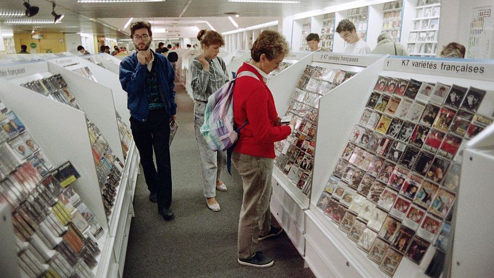 Customers look at music cassettes displayed at a store in Paris on August 28, 1987
