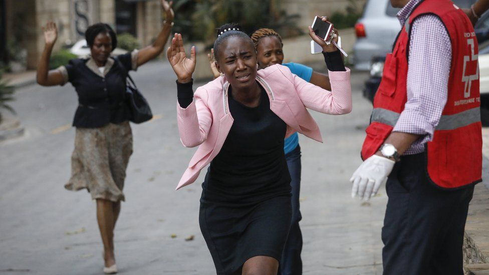 Women raise their hands as they make a run for the rescue workers during an ongoing gunfire and explosions in Nairobi, Kenya, 15 January 2019.