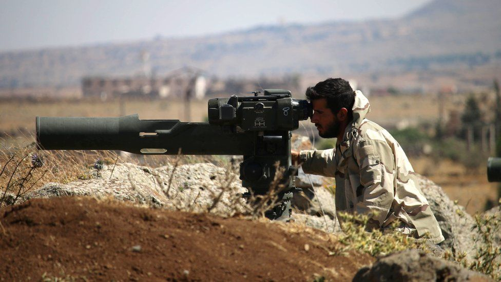 An opposition fighter looks for government forces' positions in Syria's south-western Quneitra province on June 28, 2017