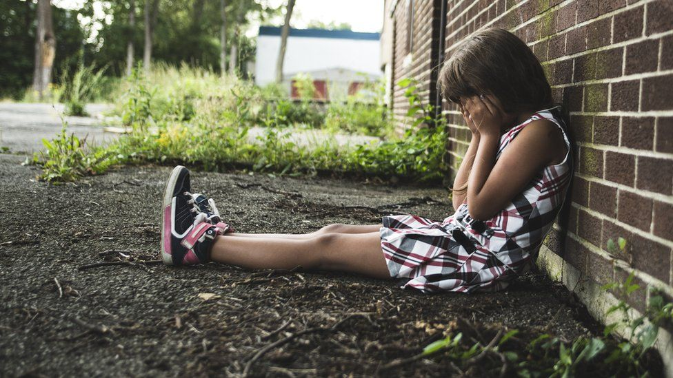Child with her head in her hands sitting on the ground