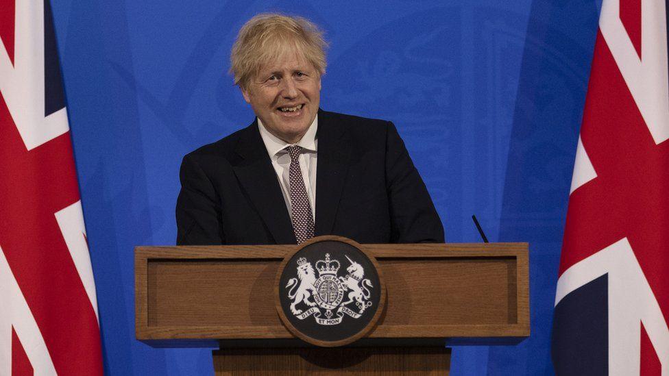 Boris Johnson smiling while giving a speech