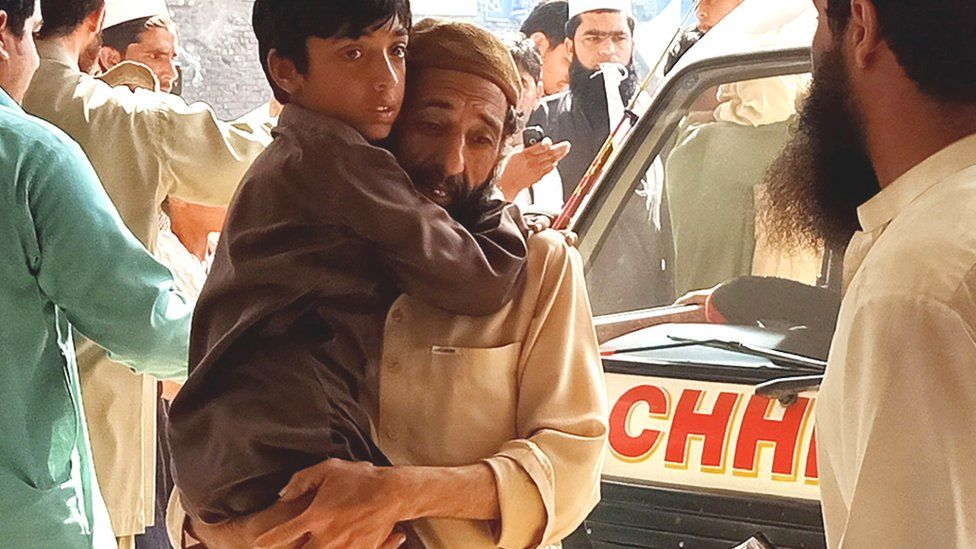 A father rushes his son to hospital after receiving a polio vaccination in Peshawar on 22 April, 2019.