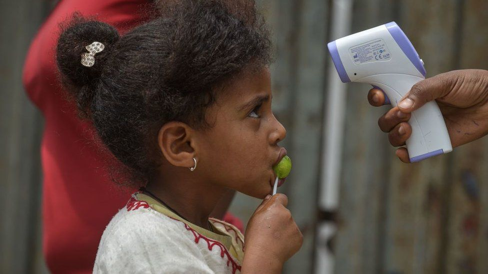 Health Extension workers of the Ministry of Health measure the tempreature of a girl during a door to door screening to curb the spread of the COVID-19 coronavirus in Addis Ababa, Ethiopia, on April 20, 2020