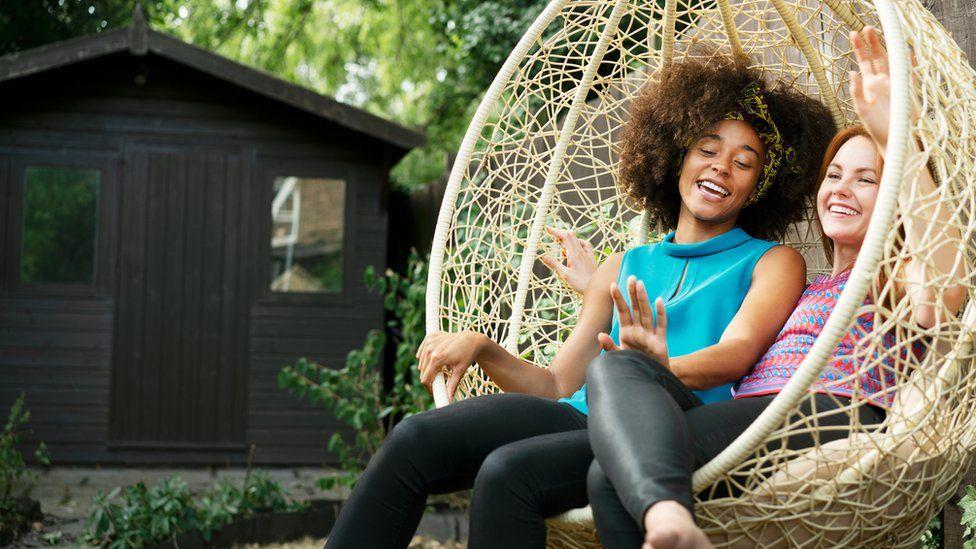 Two women on a swing seat