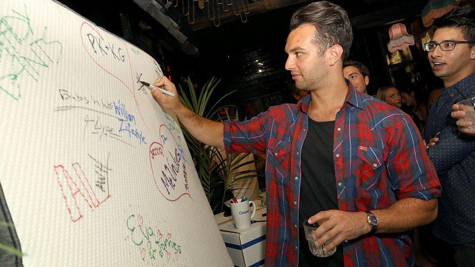 Guests sign a Casper mattress during Casper's LA celebration at Blind Dragon on July 9, 2015