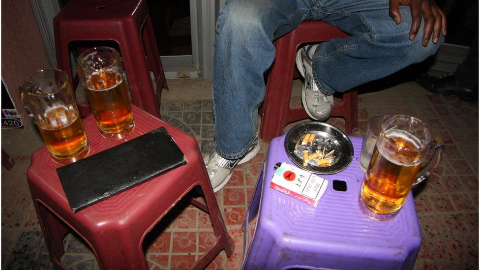 A smoker drinks and relaxes with friends outside the front door of a bar off Bole Road.