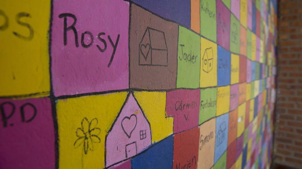 Los nombres de los miembros de la Liga de Mujeres Desplazadas y los dibujos de las casas están escritos en una pared multicolor en el centro comunitario de la Ciudad.