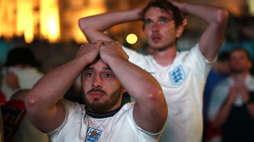 England fans react after Italy won the Euro 2020 at Trafalgar Square