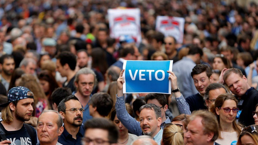 """A demonstrator holds up a banner saying """"Veto"""" during a rally against a new law passed by Hungarian parliament which could force the Soros-founded Central European University out of Hungary,"""