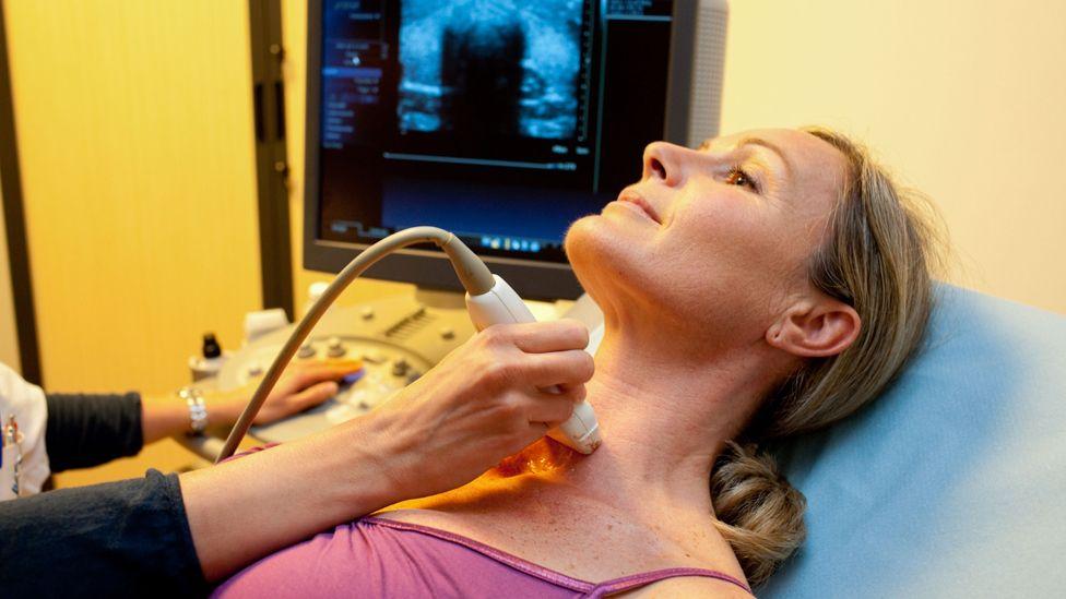 Woman undergoing a thyroid scan