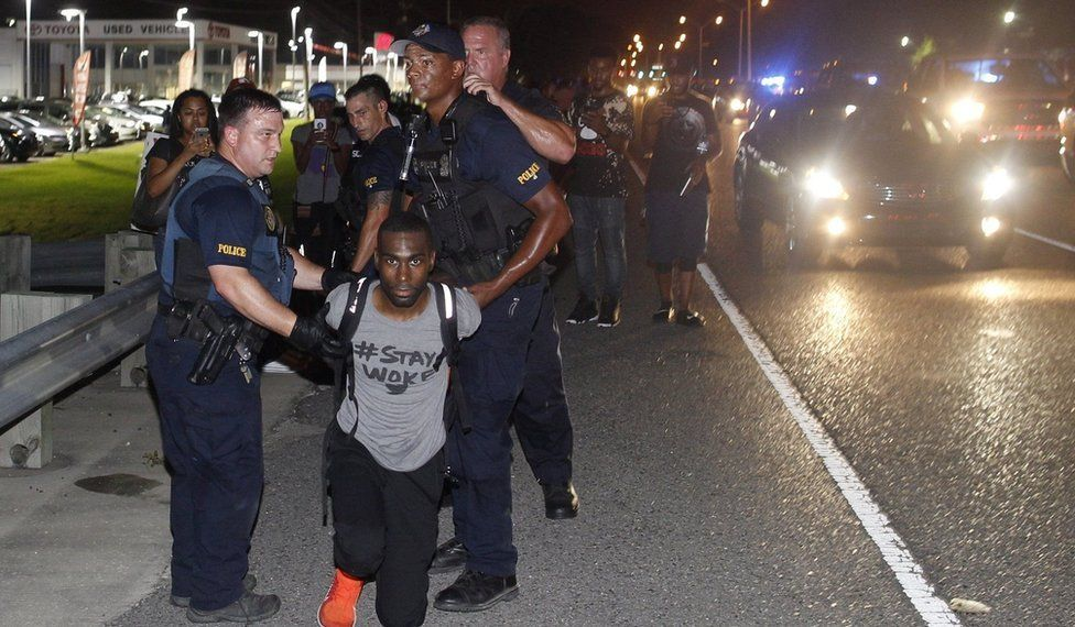 Police arrest activist DeRay McKesson during a protest along Airline Highway, a major road that passes in front of the Baton Rouge Police Department headquarters Saturday, July 9, 2016