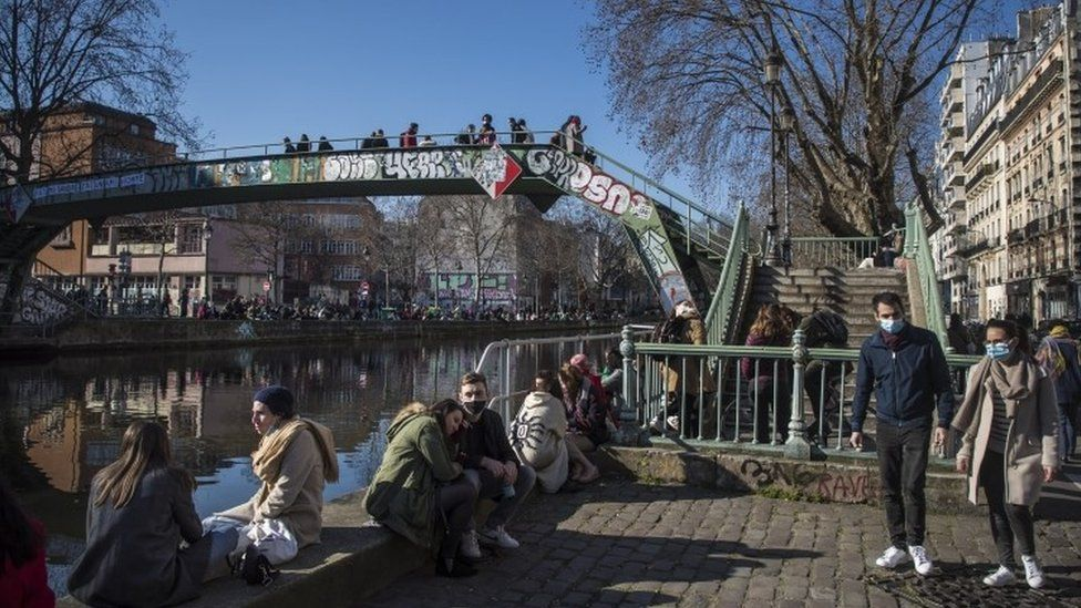 People gather along the banks of the Canal Saint Martin in Paris on Sunday 7 March