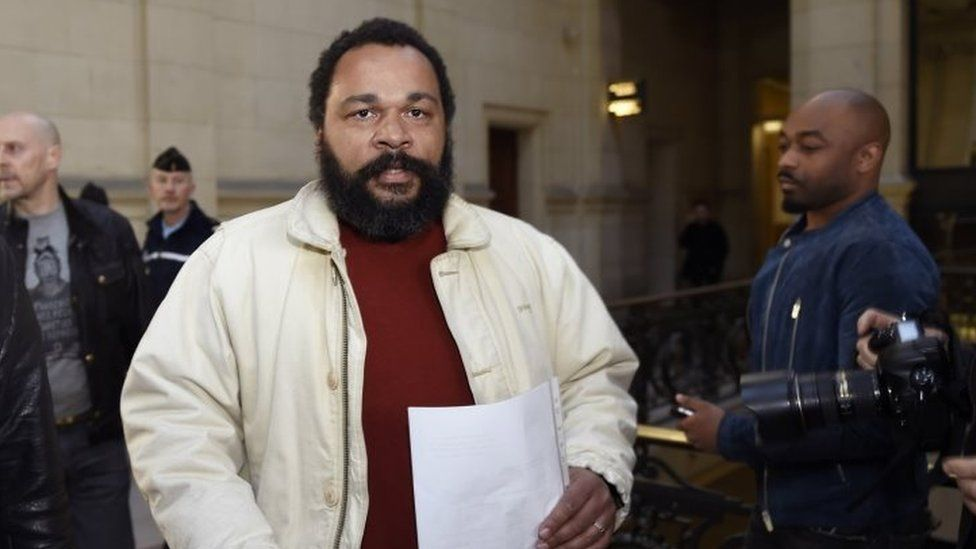 French comic Dieudonne M'bala M'bala (centre ) arriving at the Paris courthouse (12 March 2015)