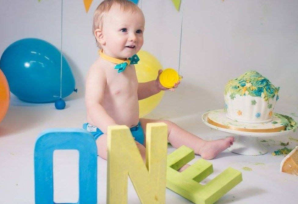 Baby Campbell posing for a photo with a cake piled with icing and balloons - also wearing a cute bow-tie