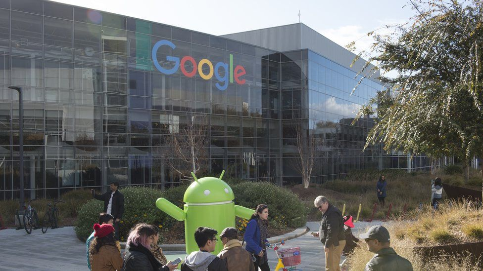 Tourists stand in front of a giant Google Android mascot at Google HQ