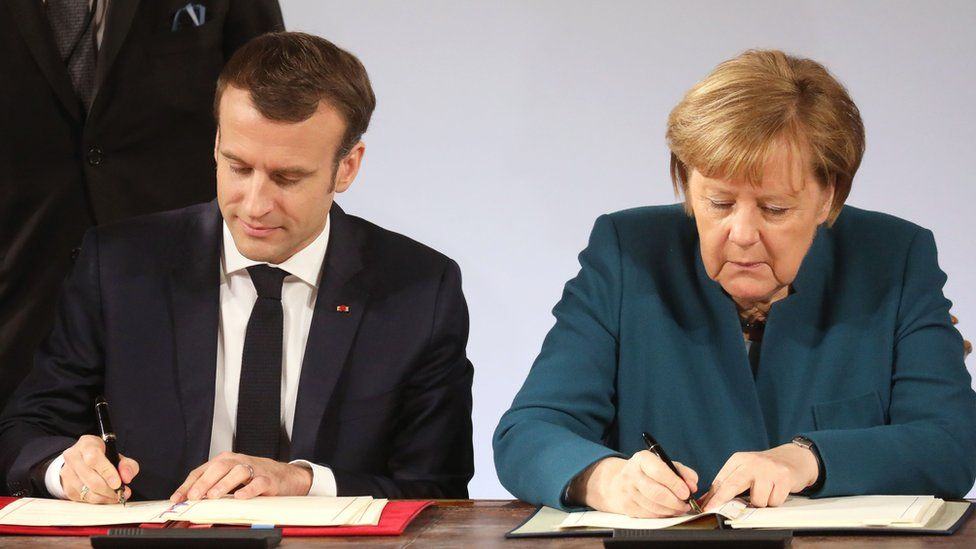 Mr Macron and Mrs Merkel sign the paper copies of the treaty