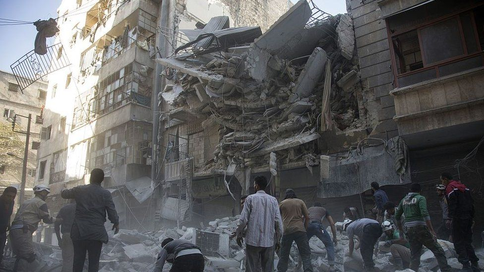 Syrian civilians and rescuers gather at site of government forces air strikes in the rebel held neighbourhood of Al-Shaar in Aleppo on September 27 2016