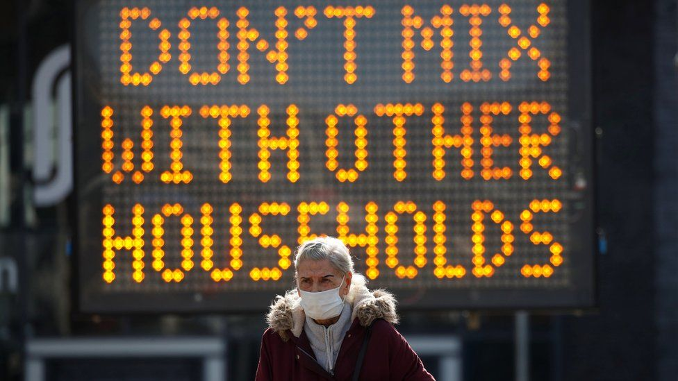 "Woman in front of sign, which reads ""Don't mix with other households"""