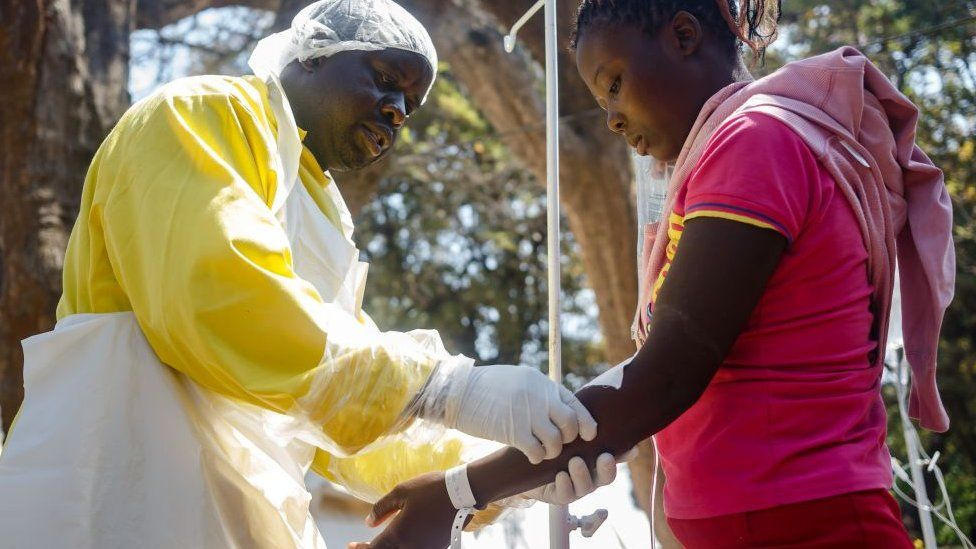 A nurse takes care of cholera patients during a visit of Zimbabwe Minister of Health,