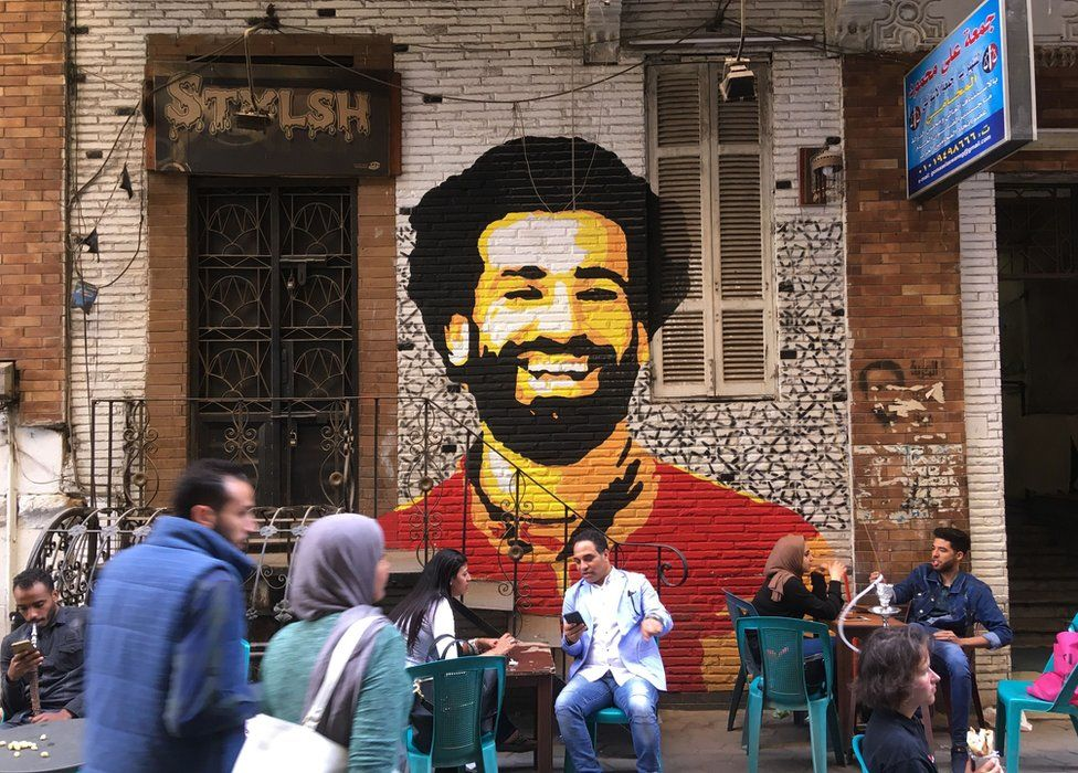 People sitting at a cafe in downtown Cairo, Egypt, with a mural depicting Liverpool FC's Egyptian striker Mohamed Salah painted in the background - 4 April 2018