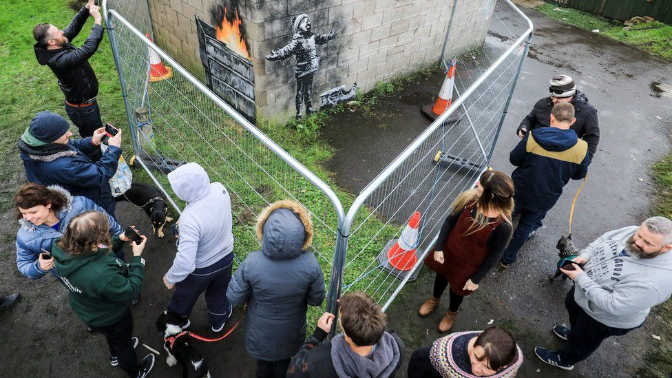Visitors take pictures of the new Banksy piece in Port Talbot