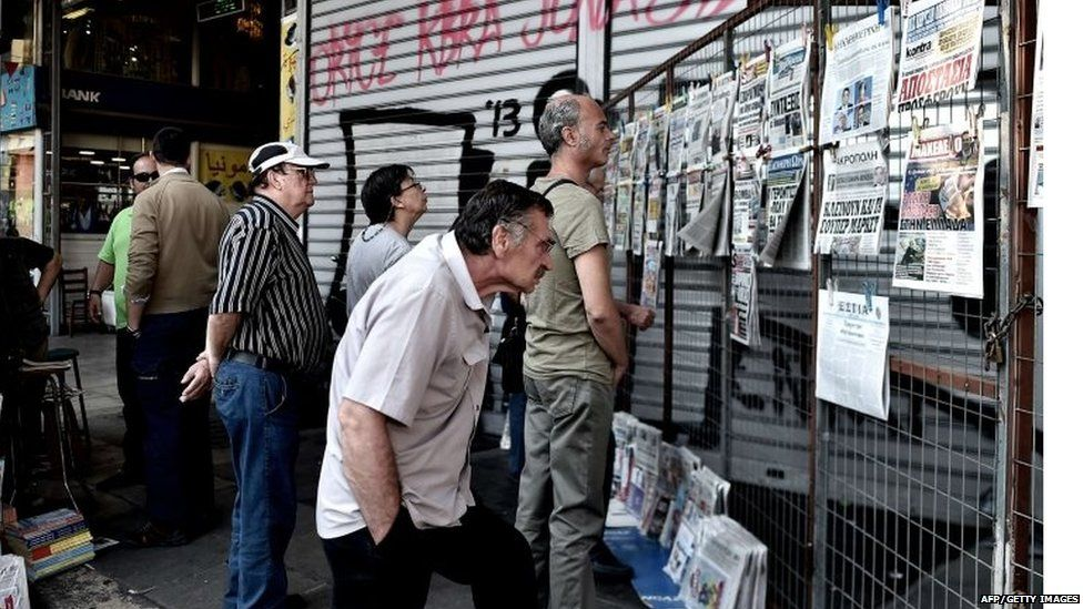 People read newspapers in central Athens on June 30, 2015.