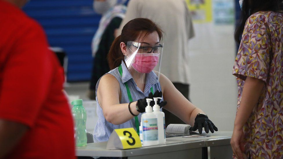 An official checks a voter's papers at a polling station in Singapore, 10 July 2020