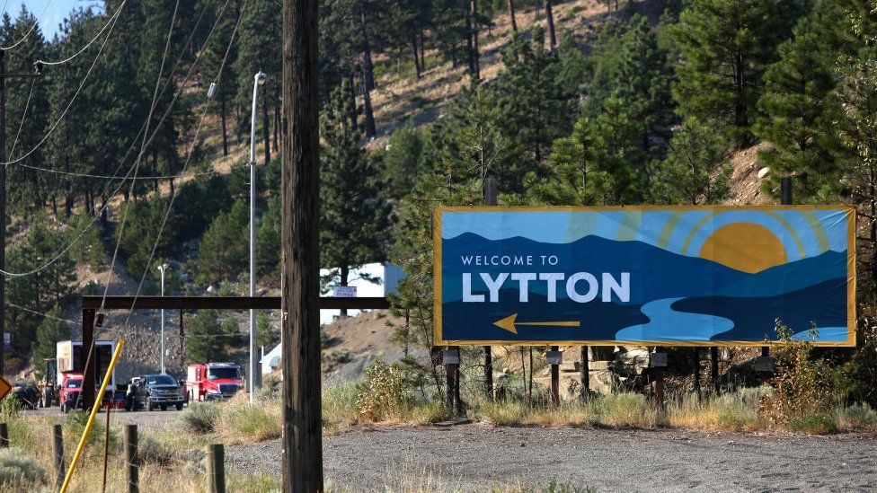 Welcome to Lytton sign is seen as smoke rises over the mountains in Lytton, British Columbia,