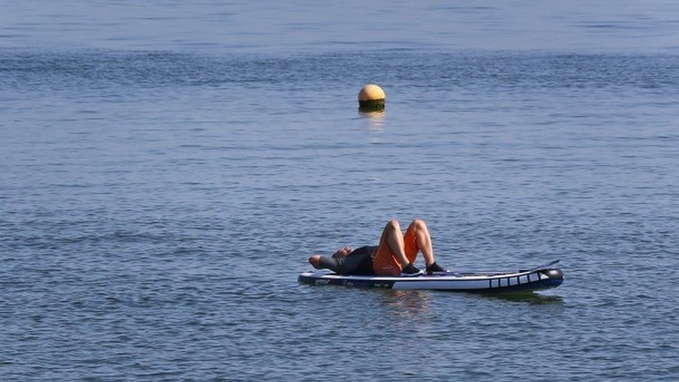 A man enjoys the warm weather on the beach in Whitstable, Kent,