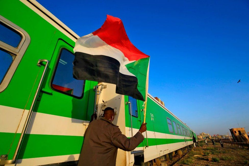 Sudanese protesters wait at a train station in Khartoum to board a train to Atbara.