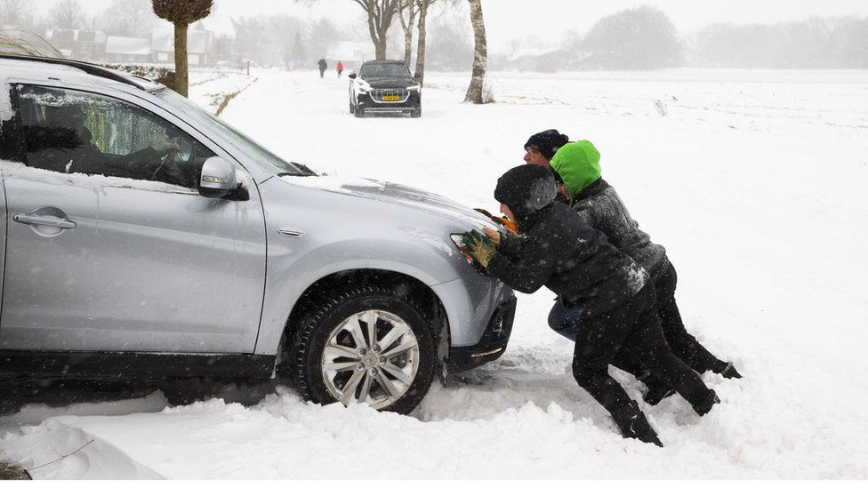 People push out a car that got stuck in a snow dune in Haarle, the Netherlands