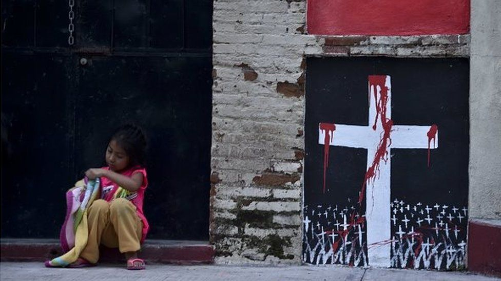 A girl sits next to a mural on 30 September , 2014, during the wake for student Julio Cesar Ramirez Nava who was killed in Iguala,