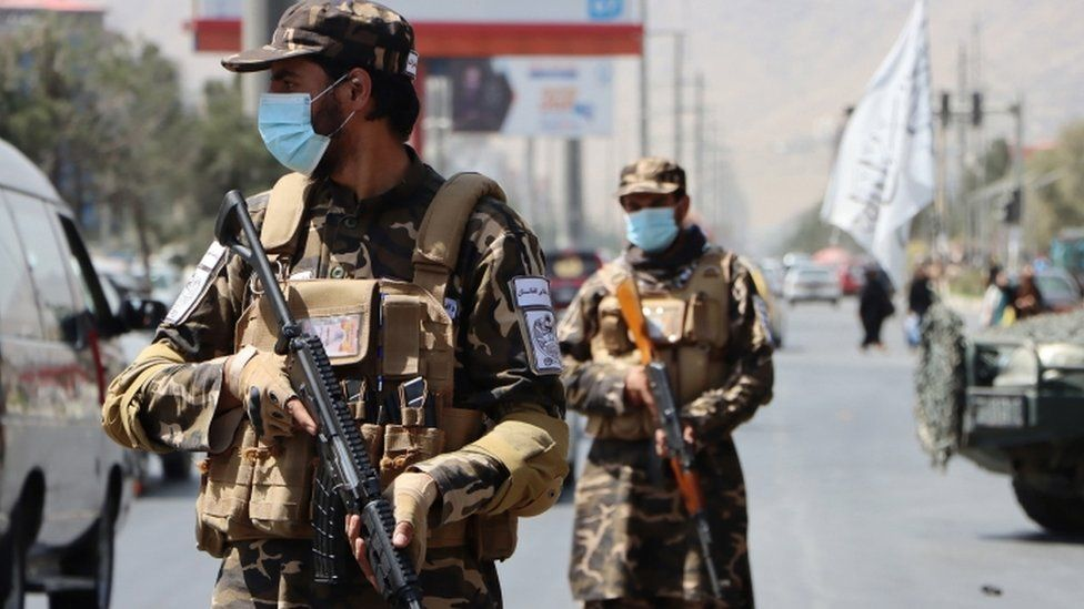 Taliban forces stand guard at a roadside checkpoint in Kabul, Afghanistan