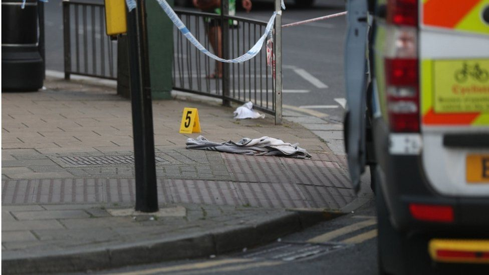 An item of clothing lies on the pavement at the junction of Palmerston Road and Wealdstone High Street