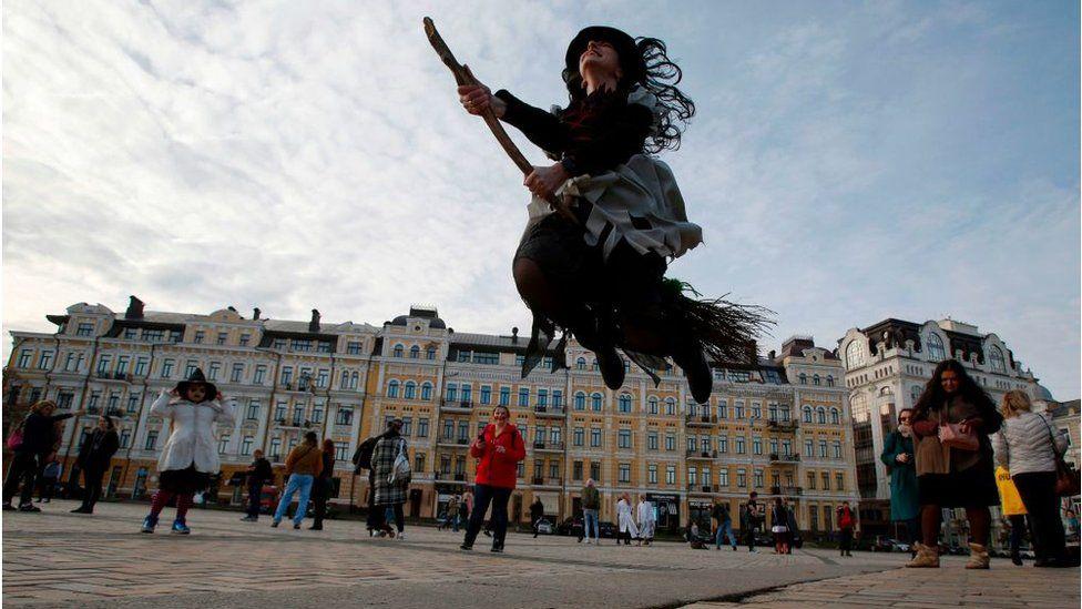 Дівчина в костюмі відьми немов летить на мітлі на Софійській площі в Києві