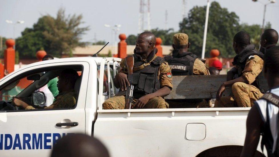 Gendarmes drive by anti-coup protesters in Ouagadougou, Burkina Faso, September 22, 2015.