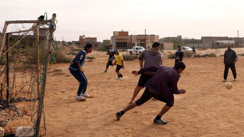 Young people in Libyan city of Sirte play football upon returning there after the Isis group has been driven out away by government troops