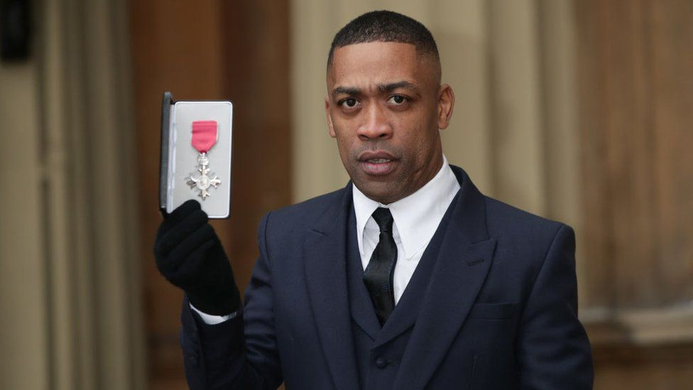 Wiley, also known as Richard Cowie, poses with his medal after being appointed an MBE in 2018