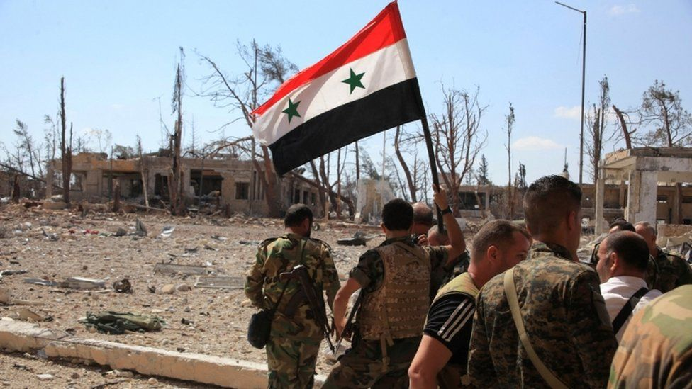 Forces loyal to President Assad walk through Aleppo as one of them holds up a Syrian national flag