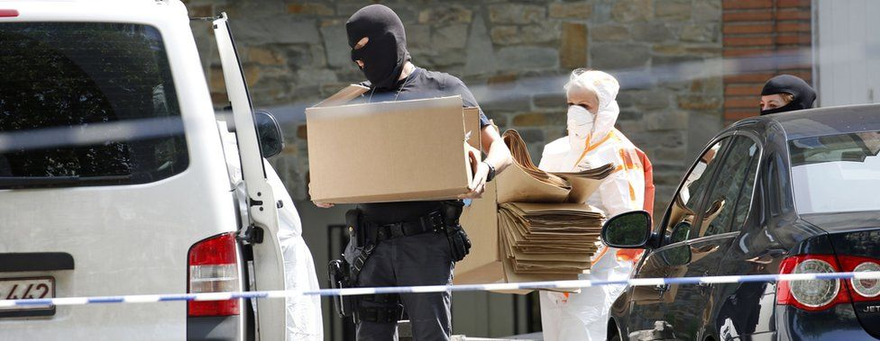Forensic police leave the suspect's home in Molenbeek with several boxes (21 June)