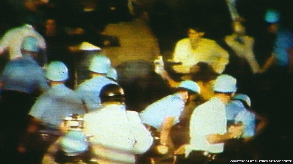 A group of policemen in riot gear confronting a crowd at the convention
