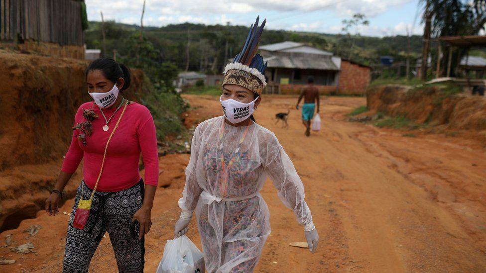 Vanderlecia and a friend walk along a road in Parque das Trios